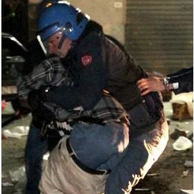 Un poliziotto placca un immigrato (Ansa)