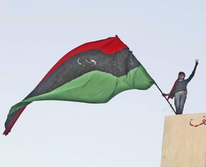 Un dimostrante sventola la bandiera libica (ansa)